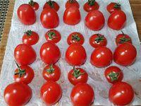 1 - Mettre les oeufs à cuire dans une casserole d'eau bouillante pendant 9 mn. Laver et sécher les mini tomates en gardant les pédoncules. Couper la partie supérieure, épépiner l'intérieur, retourner les tomates et leurs chapeaux sur du papier absorbant. Emietter le pain de mie dans un récipient, verser dessus le vinaigre, bien écraser à la fourchette. Peler et dégermer l'ail et l'intégrer pressé à la préparation.