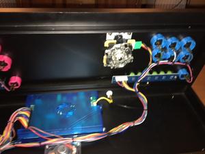Un petit coup d'oeil sous le capot ? Au centre on voit la carte multijeux, Pandora's Box 4S + qui comprend 815 jeux d'arcade. Un haut parleur. Le câblage est propre et bien organisé.