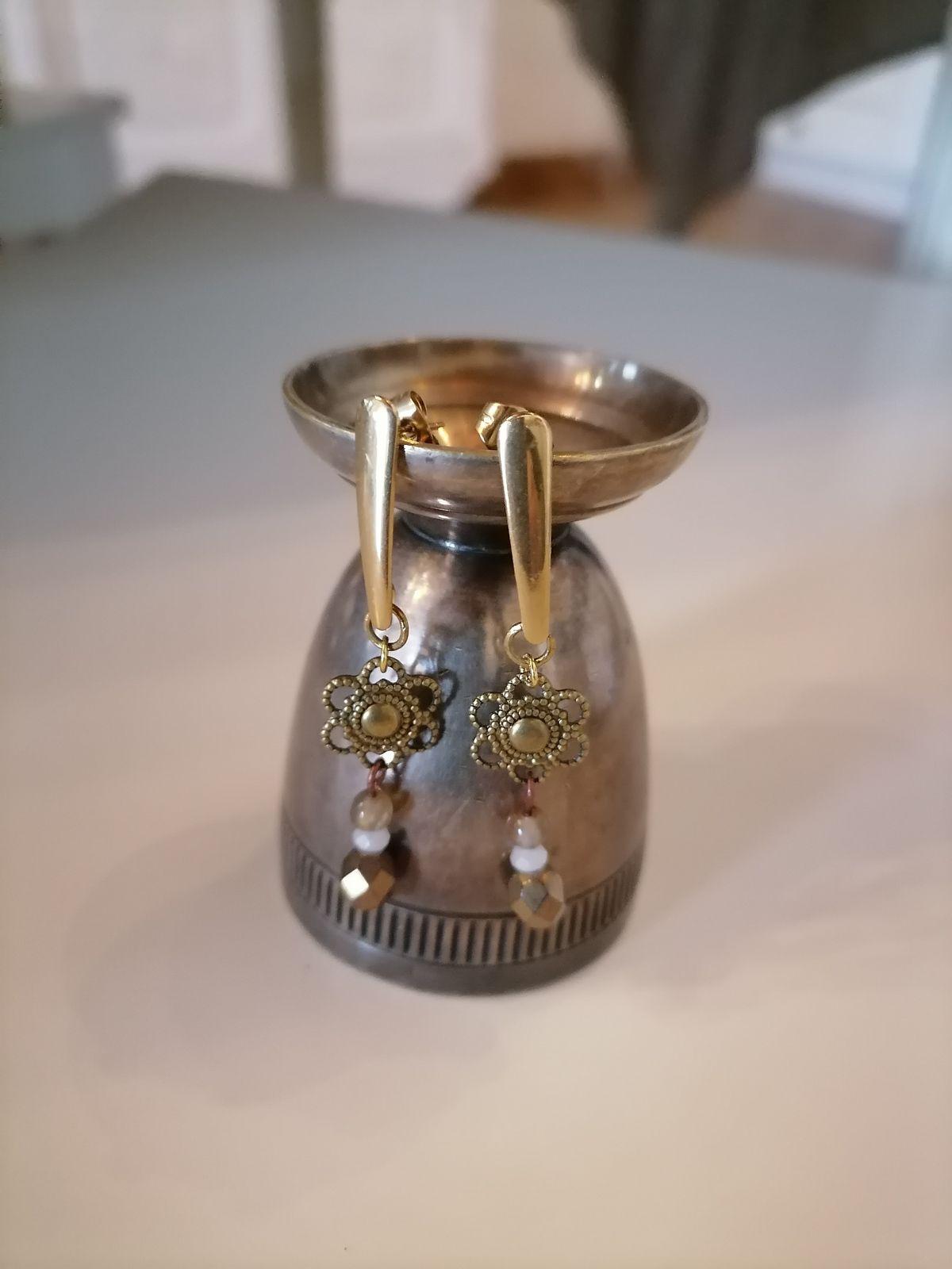 Acier doré et métal vieilli, cristaux de verre pour ces boucles pendantes.
