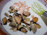 2 - Dans un saladier, préparer la pâte à galette en versant successivement : la farine, le sel, la levure chimique, mélanger. Incorporer progressivement l'eau gazeuse et mélanger jusqu'à obtenir une préparation bien lisse. Ajouter les crevettes, les moules, le poulpe, le piment coupé en morceaux (facultatif) et l'oignon blanc émincé, mélanger, terminer en ajoutant le poivre moulu. Verser un filet d'huile d'arachide dans une poêle préalablement chauffée sur feu doux.