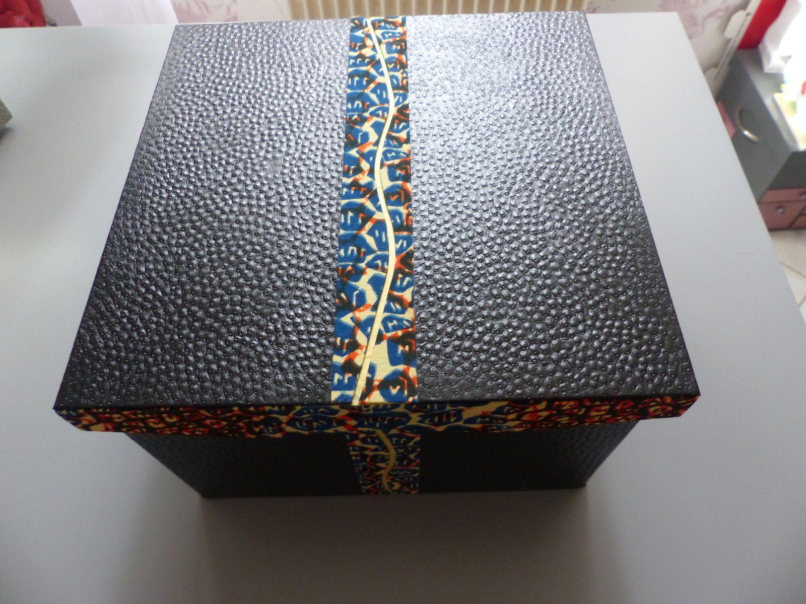 Fermée : devant, derrière et dessus, avec rappel de tissu sur les côtés et le dessus du couvercle, sur le panneau arrière ainsi que pour le noeud de fermeture
