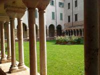 Le cloître roman derrière lequel on aperçoit le clocher blanc du Duomo.