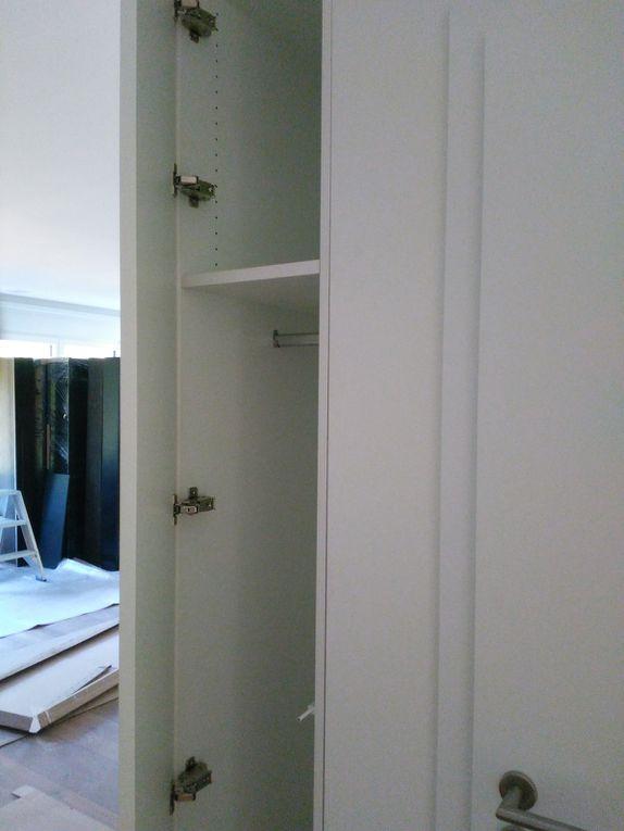Mobilier sur mesure de fabrication propre en Statifié structuré  blanc composé d'un espace étagère - bibliothèque (tablettes amovibles sur système 32) - 1 espace réservé pour le piano - et 1 espace fermé (ouverture porte par système Tip - On / coupe à 45 ° pour invisibilité de la porte) rangement penderie sur le côté.