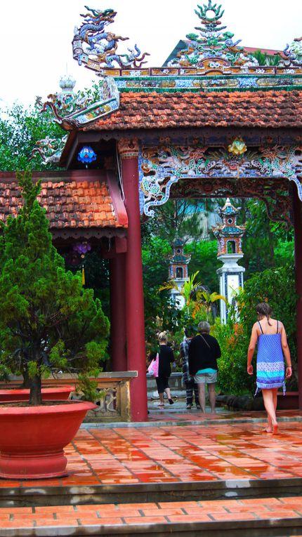 """Da Lat : Après 4 h de route sous une pluis battante à l'arrivée nous découvrons la montagne (1500m) avec ses forêts de pins.C'est une journée consacrée à la découverte de la ville de Da Lat. Nous avons pris le téléphérique érigé en 2006 pour visiter le monastère bouddhiste de TRUC LAM. Le téléphérique permet de se rendre mieux compte de la diversité des paysages où s'entremêlent les forêts de pins (plantés par les français pendant la colonisation), les constructions anciennes (types maisons coloniales), les constructions modernes, les serres horticoles, et les champs en terrasse où l'on cultive des…fraises, des artichauts et toutes variétés de légumes que l'on ne peut cultiver ailleurs au Viêt-Nam. C'est un grand domaine fleuri, très ombragé, entretenu par les moines. Nombreux bonsaïs qui régaleront les collectionneurs et les passionnés. Relativement récent il est très bien entretenu.  Puis visite de l'ancienne gare de Da Lat sous la pluie.  Mais quelle chance de voir des jeunes mariés en costume traditionnel qui viennent se faire prendre en photo sur les marches du vieux train et de pouvoir également assister au départ d'un petit train qui arpente 6 ou 7 kms dans la campagne ! Nous visitons en fin de journée le Palais de BAO DAI, dernier roi du Viêt Nam, qui a laissé une demeure imposante, avec de multiples pièces et ses collections de photographies et de souvenirs de ce passé colonial. Dans l'après – midi le bus nous dépose devant la «  Crazy House ». Cette drôle de demeure se situe  entre le Palais Idéal du facteur Joseph Cheval, décors du cinéma expressionniste allemand, architecture ondulante et organique d'Antonio Gaudí et formes liquides issues de peintures de Salvador Dalí. Hằng Nga est assurément l'un des hôtels les plus insolites au monde..(pour une prochaine visite à Da Lat, pour 40000 dongs """"seulement une nuit dans cet hôtel,  on passe un bon moment). Au final nous partons à la découverte de la vallée de l'amour..  Comment vous décrire le lieu ? : vous ê"""