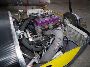 L'appareil rentre dans le hangar. Une photo du moteur Bombardier Rotax.
