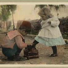 A young boy polishes his girlfriend's shoes