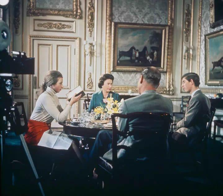 """Les caméras de la BBC filment le déjeuner de la reine Elizabeth II, du prince Philip et de leurs enfants Charles et Anne à l'occasion du tournage du documentaire """"Royal Family"""", en 1969 au château de Windsor. (HULTON ARCHIVE / HULTON ROYALS COLLECTION / GETTY IMAGES)"""