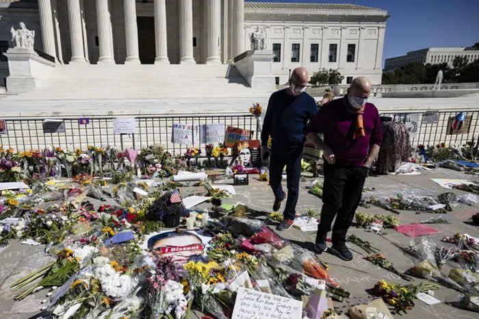 Michael Widomski (à gauche) et David Hagedorn (à droite) laissent une photo de Ruth Bader Ginsburg à leur mariage devant la Cour suprême des États-Unis le 20 septembre 2020 à Washington, DC. La juge Ginsburg a célébré leur mariage en 2013, deux ans avant que la Cour suprême n'ouvre la voie aux mariages homosexuels dans tout le pays en 2015. Samuel Corum/AFP