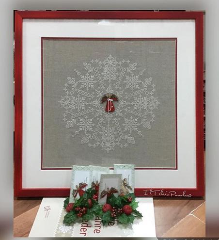 Un grande fiocco di neve a punto croce  con al centro un angioletto in 'legno' rosso