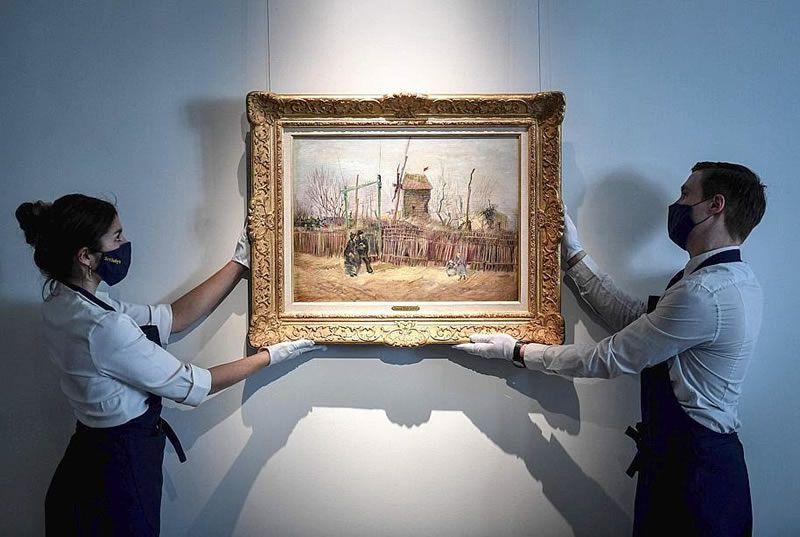 """Sur cette photo d'archive prise le 24 février 2021, deux employés exposent un tableau intitulé """"Scène de rue à Montmartre"""" du peintre néerlandais Vincent Van Gogh, à la maison de vente aux enchères Sotheby's à Paris. Photo Stephane DE SAKUTIN / AFP"""