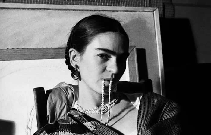Frida Kahlo mordant son collier, à New York, 1933. — Lucienne Bloch