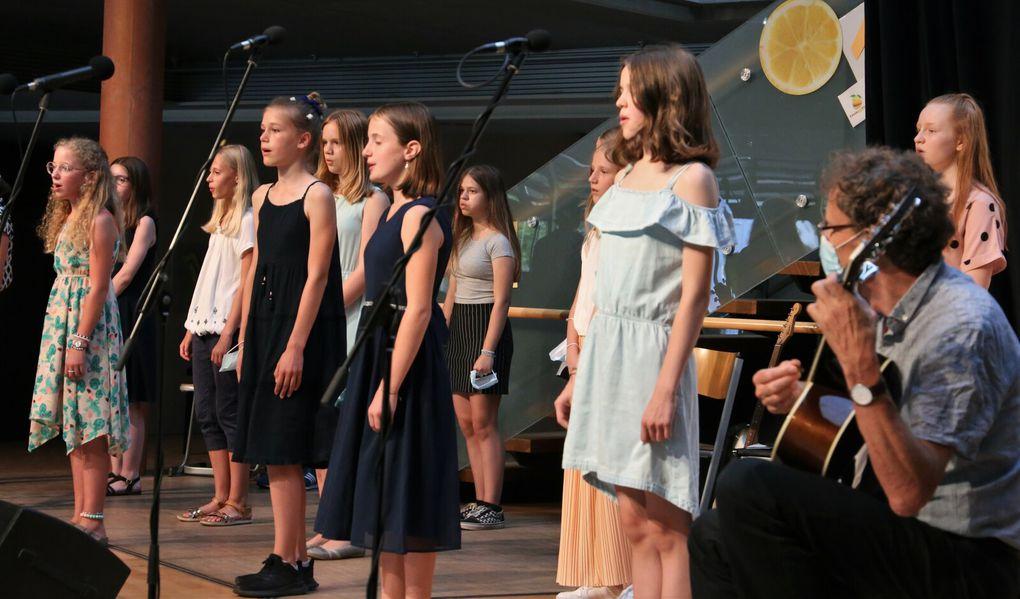"""Das Konzert eröffnete der von Claudia von der Goltz geleitete Chor der Klassen fünf bis sieben mit """"Memories"""" von Maroon 5 und """"Probier's mal mit Gemütlichkeit"""" von Terry Gilkyson, begleitet von Bernhard von der Goltz an der Gitarre (1. Lied) und am Klavier (2 Lied)."""