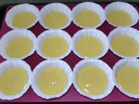 2 - Bien mélanger le tout au fouet, puis incorporer le yogourt et la farine tamisée (préalablement mélangée au sachet de levure chimique) en remuant bien pour obtenir une pâte bien lisse. Disposer des caissettes en papier dans les emplacements d'un moule à muffins en silicone (ou autre), et les remplir au 3/4 avec la préparation. Disposer une  pincée de sucre semoule au milieu de chaque madeleine et mettre au four th 6 pour 15 min environ en surveillant.
