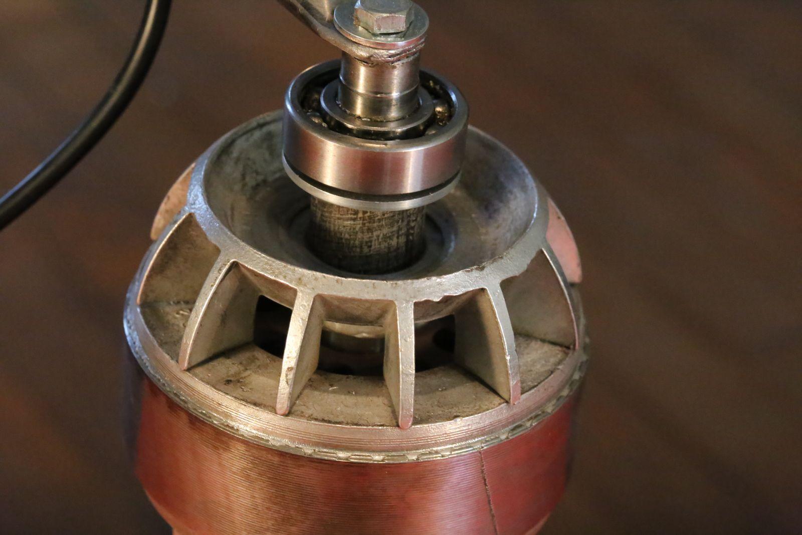 Création d'une lampe unique avec d'anciens objet de récupération : parabole de chauffage Calor, moteur électrique, axe de roue de voiture