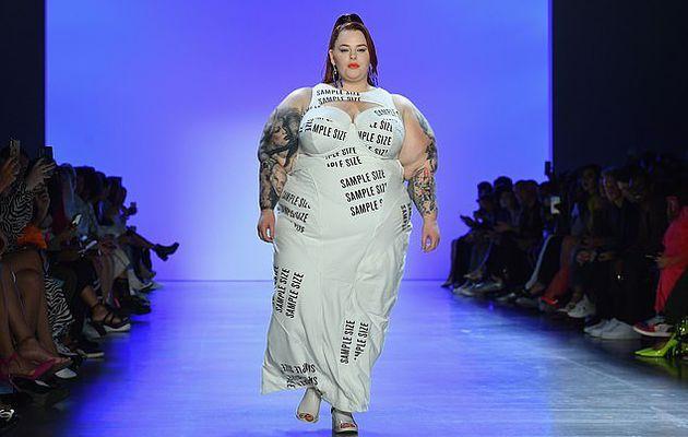 La mannequin grande taille Tess Holliday fait une déclaration dans une robe blanche découpée avec les mots «taille de l'échantillon» alors qu'elle défile sur le podium pendant la Fashion Week de New York