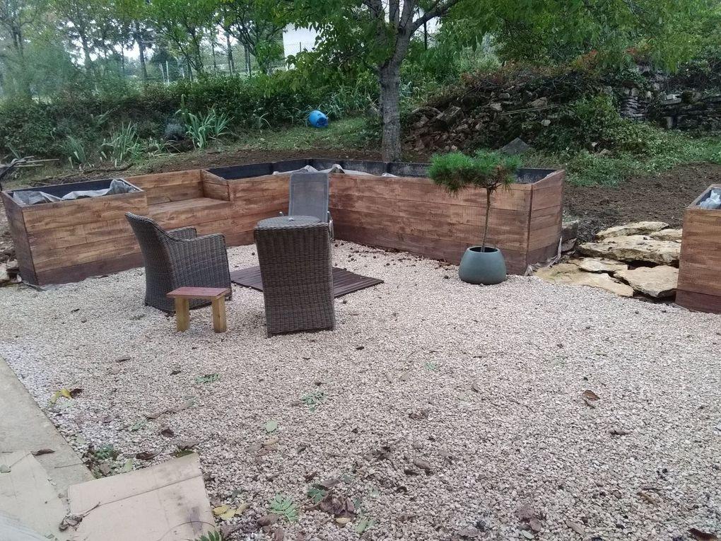 Aménagement d'une terrasse en cailloux avec bac en bois.