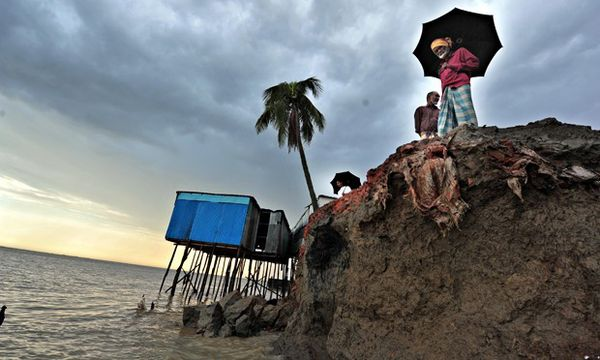Cost of Climate change: Coastal erosion in Bangladesh as Padma River continues to devour banks Residents look over the banks of the Padma River as they erode, in Dhaka, Bangladesh. A UN report says cost of helping countries adapt to the effects of climate change will be hundreds of billions of dollars.