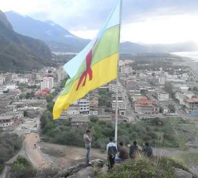 un géant drapeau de Tamazgha flotte sur la comune de Melbou