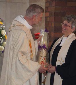 Pfarrerin Silke Wolfrum gratuliert und schenkt die Osterkerze für die Kuratie-Kirche.