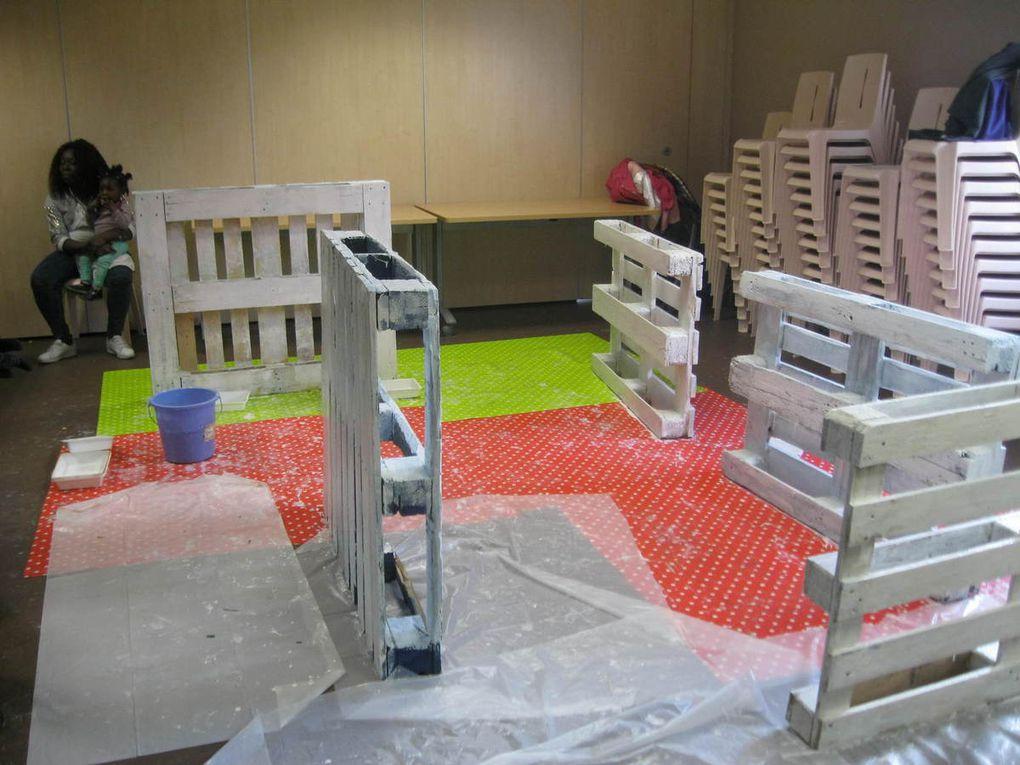 Les familles de Récré'actions mettent des palettes en peinture pour végétaliser les murs de la Maison de Quartier de la Briquette