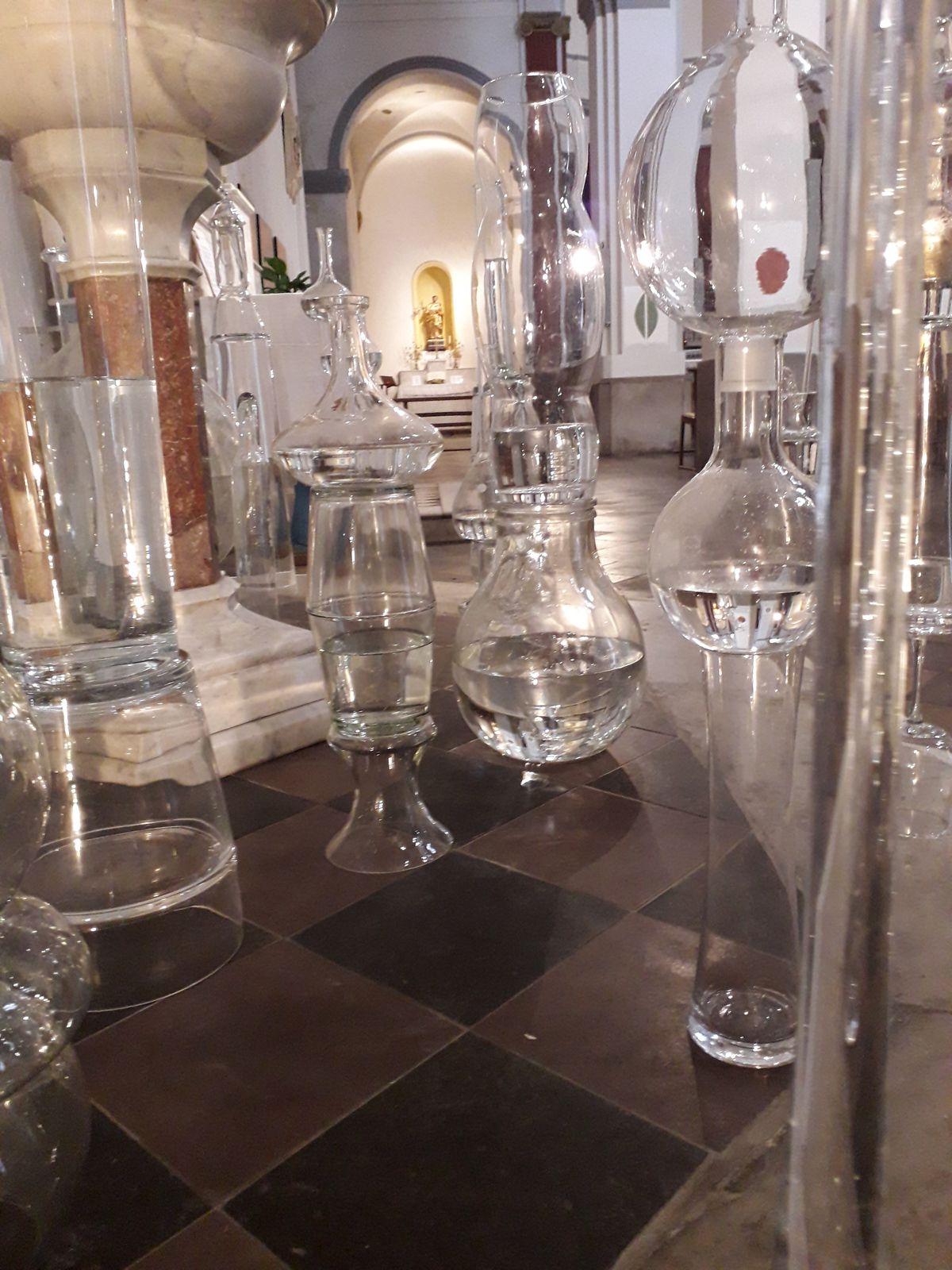 Françoise Rod présente une installation tout en fragilité et en équilibre autour du baptistère. Les vases, verres, décanteurs et damesjeanne sont empilés les uns sur les autres. Certains contiennent de l'eau.